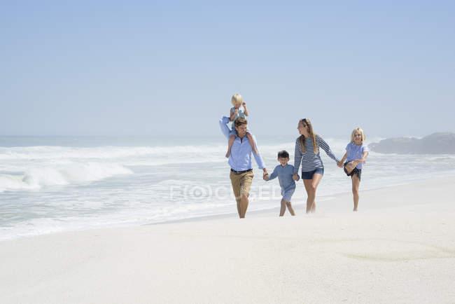 Família feliz com crianças andando na praia — Fotografia de Stock