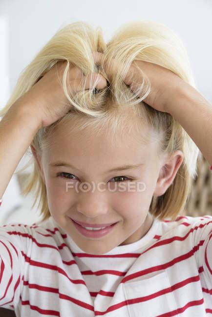 Retrato de menina arranhando o cabelo e olhando para a câmera — Fotografia de Stock