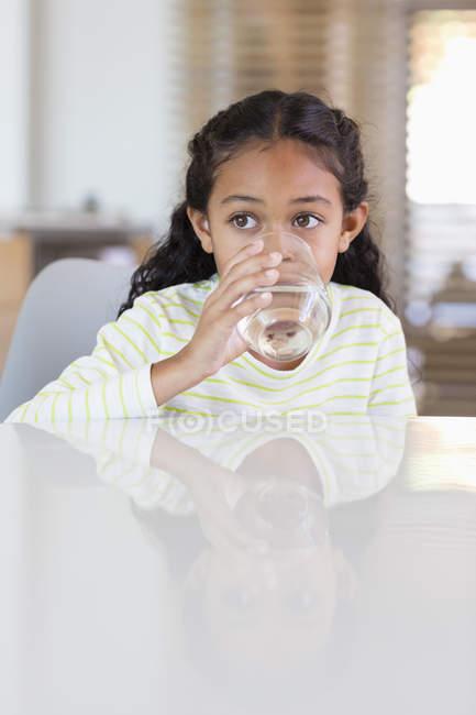 Niña bebiendo agua de vidrio en la mesa en casa y mirando hacia otro lado - foto de stock