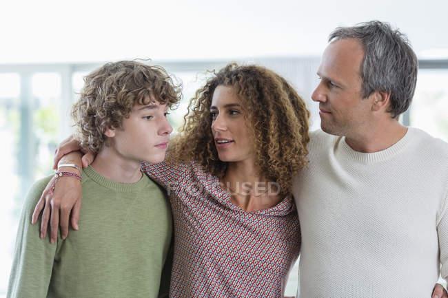 Retrato de familia feliz juntos de pie en casa - foto de stock