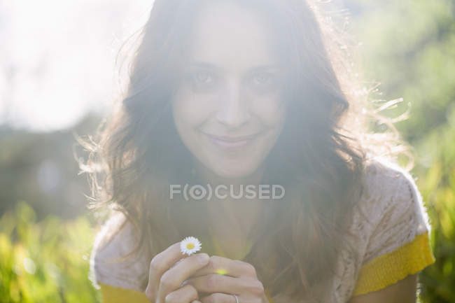 Smiling woman in sunny nature holding small daisy flower — Stock Photo