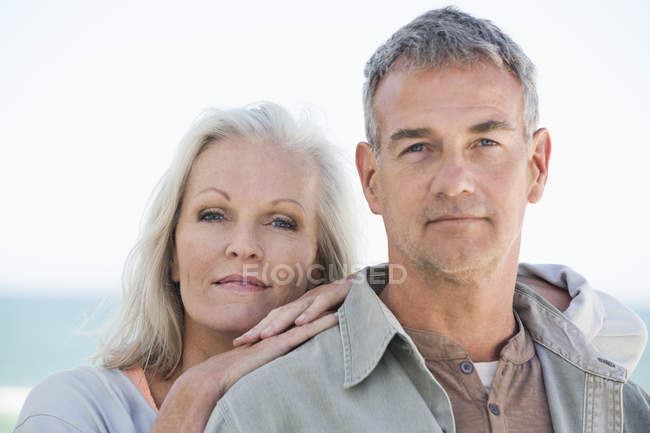 Portrait of happy relaxed couple standing on beach — Stock Photo