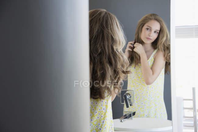 Adolescente examinando el cabello en el espejo - foto de stock