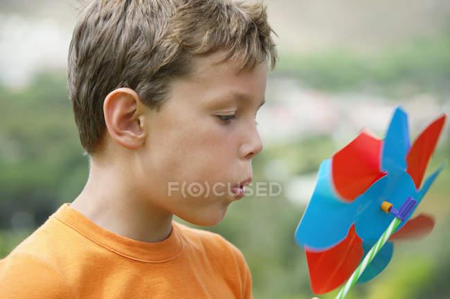 Close-up de menino soprando no pinwheel colorido ao ar livre — Fotografia de Stock