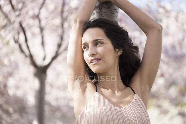 Relaxed woman smiling while leaning on tree trunk — Stock Photo