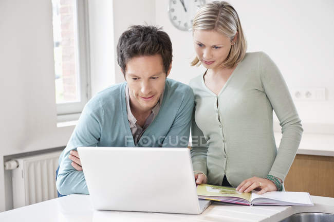 Concentrated couple working on laptop at desk — Stock Photo