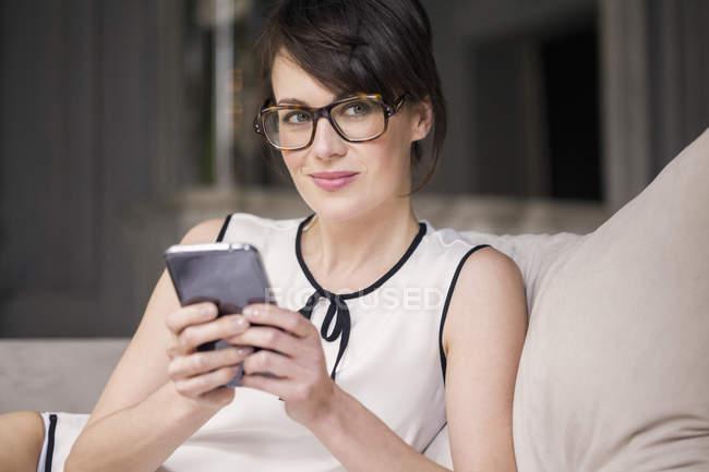 Nachdenkliche Frau mit Brille hält Smartphone in der Hand und schaut auf Sofa weg — Stockfoto