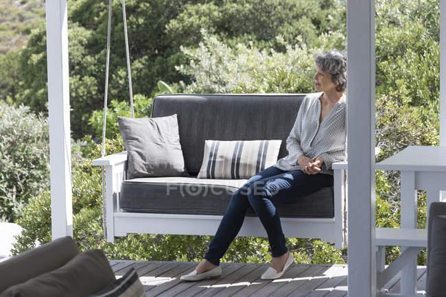 Счастливая женщина отдыхает на качелях на крыльце — стоковое фото
