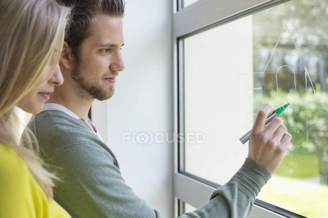 Woman looking at  architect drawing design on window glass — Stock Photo