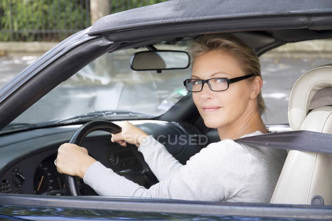 Nahaufnahme einer lächelnden Frau mit Brille am Steuer — Stockfoto