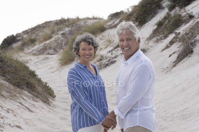 Happy senior couple standing on sandy beach holding hands and looking at camera - foto de stock