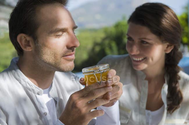 Homme sentant la marmelade avec femme regardant dans la nature — Photo de stock