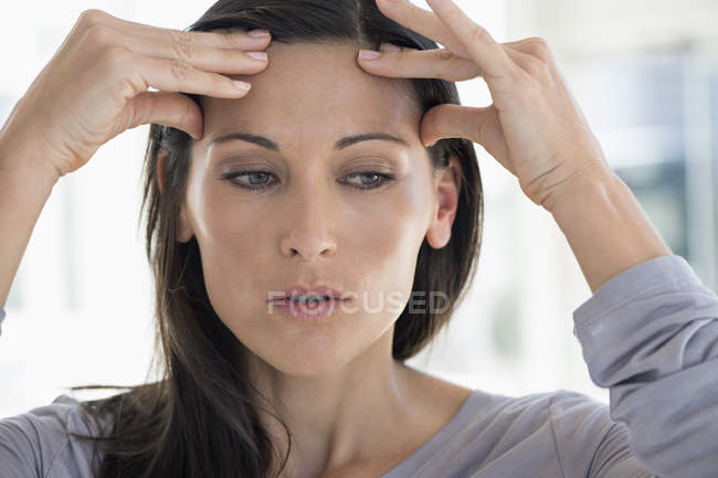 Close-up of woman suffering from headache on blurred background — Stock Photo