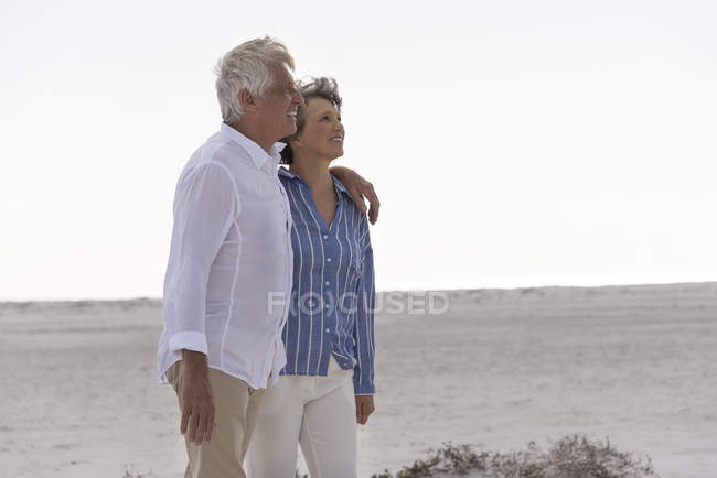 Happy senior couple walking on beach together — Stock Photo