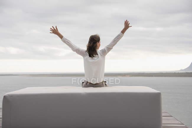 Вид сзади женщина сидит на Османской на берегу озера — стоковое фото