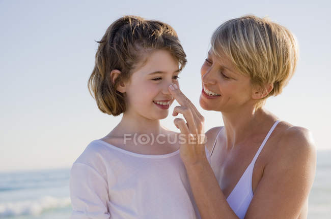 Woman with daughter enjoying vacations on beach — Stock Photo