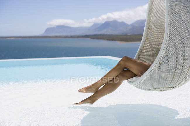Legs of woman relaxing in wicker swing at poolside — Stock Photo