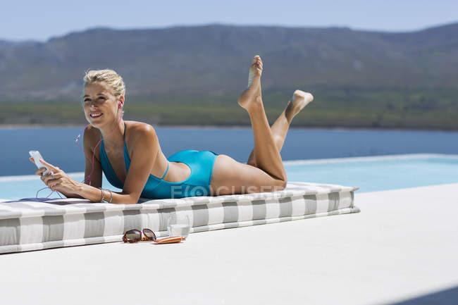 Relajado mujer joven escuchando música con el smartphone a la piscina - foto de stock