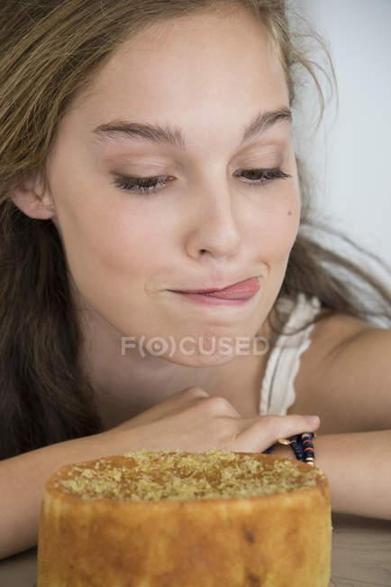 Adolescente ragazza sporgente lingua mentre guardando la torta — Foto stock