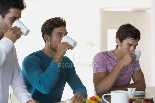 Close-up of three friends drinking coffee in kitchen — Stock Photo