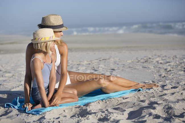Femme souriante et fille dans des chapeaux assis sur la plage de sable — Photo de stock