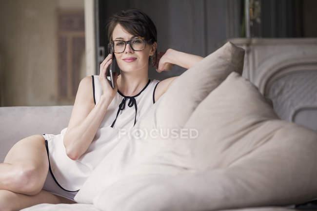 Lächelnde Frau sprechen auf Mobile Phone auf dem Sofa zu Hause — Stockfoto
