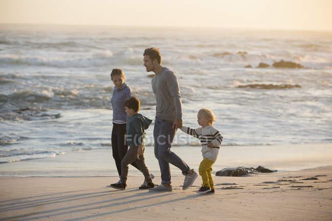 Passeggiata in famiglia sulla spiaggia sabbiosa al tramonto — Foto stock