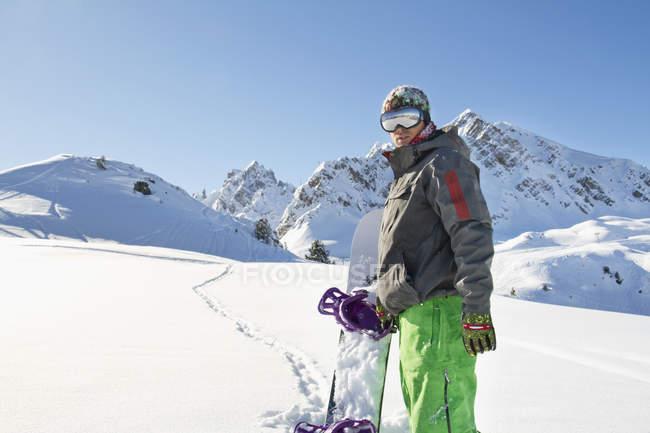 Молодой человек с сноуборд стоя в снежные горы. — стоковое фото