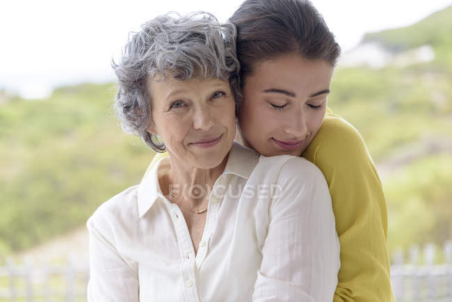 Portrait of loving young woman hugging mother outdoors — Stock Photo