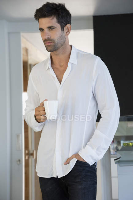 Thoughtful man enjoying cup of coffee at home — Stock Photo