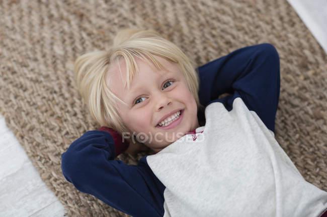 Glücklicher kleiner Junge legt sich auf Korbteppich — Stockfoto