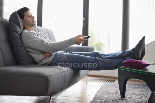 Homme couché sur le canapé et le changement de canaux avec télécommande — Photo de stock