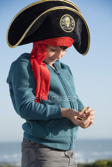 Pirate little boy holding coins outdoors — Stock Photo