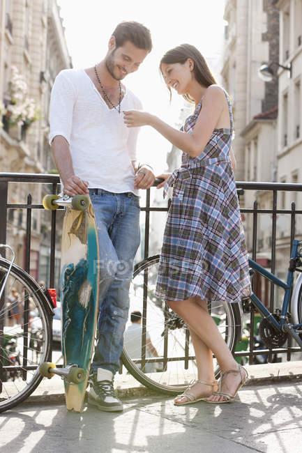 Femme regardant le collier de l'homme dans la rue en ville — Photo de stock