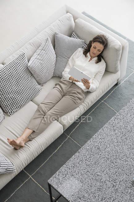 Женщина лежит на диване дома и использует цифровой планшет — стоковое фото
