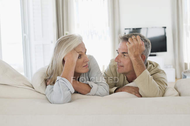 Portrait of smiling senior couple resting on bed at home and looking at each other — Stock Photo