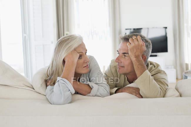 Портрет усміхнений старший пара, лежачи на ліжку у себе вдома і дивляться один на одного — стокове фото