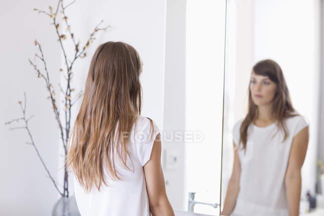 Mujer joven y seria mirando en el espejo en el baño - foto de stock