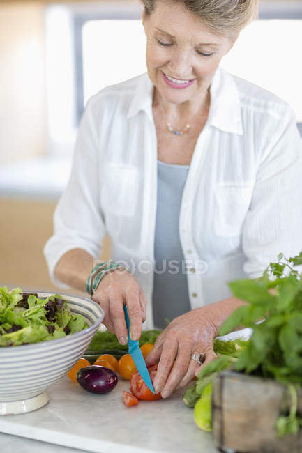 Happy senior woman cutting vegetables in kitchen — Stock Photo