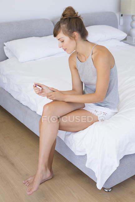 Жінка сидить на ліжку і перевірка тест на вагітність — стокове фото