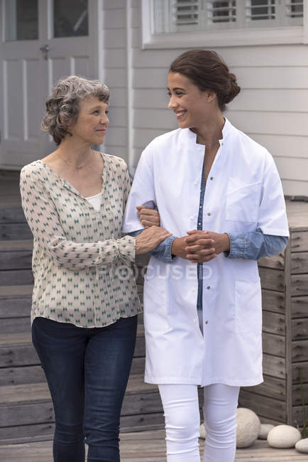 Female nurse assisting smiling senior woman in nursing home — Stock Photo
