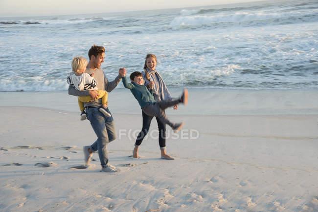 Счастливая семья веселится на пляже на закате — стоковое фото
