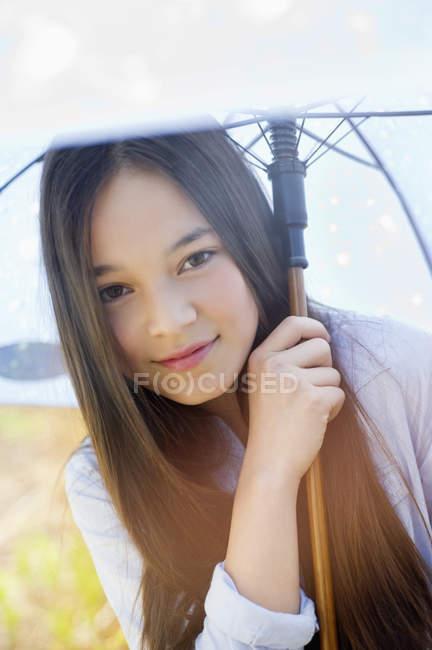 Портрет счастливой девочки-подростка, держащей зонтик на открытом воздухе — стоковое фото
