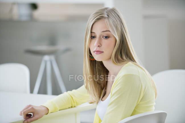 Schwere jungen blonden Frau sitzt im Zimmer und wegsehen — Stockfoto