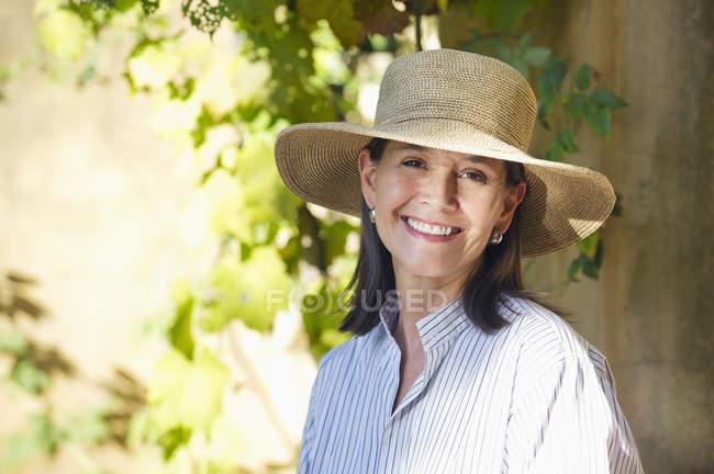 Porträt einer Seniorin mit Strohhut und einem Lächeln im Garten — Stockfoto