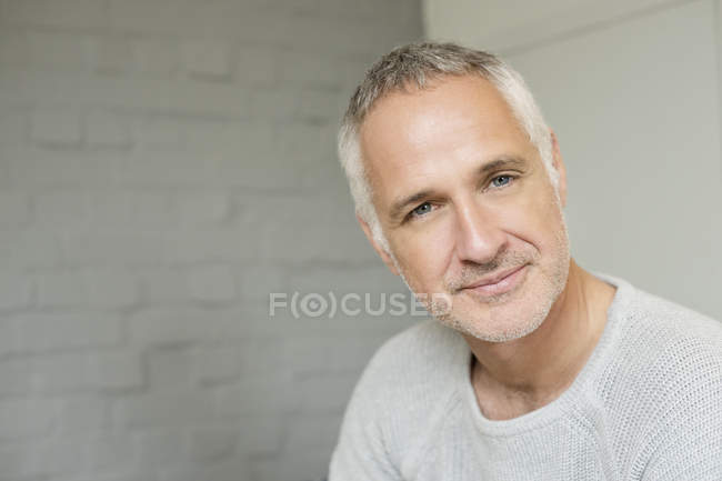 Portrait of happy grey haired man against brick wall — Stock Photo