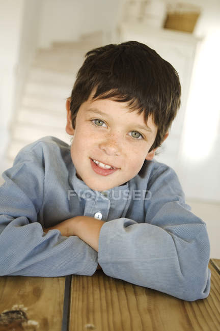 Little freckle boy smiling and looking at camera at wooden table — Stock Photo