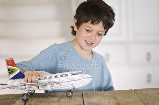 Little boy playing with model aeroplane at home — Stock Photo