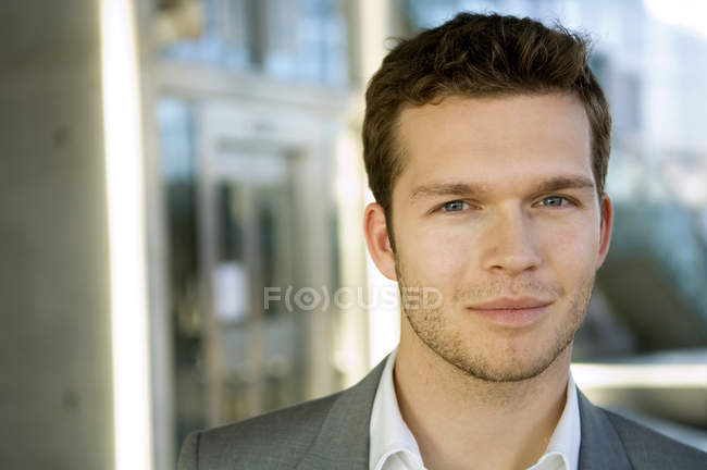 Portrait of young businessman smirking on blurred background — Stock Photo