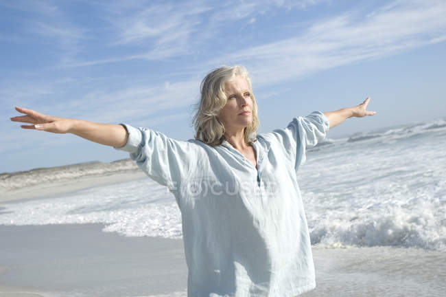 Woman with arms outstretched doing yoga on beach — Stock Photo